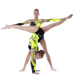 Two woman high skill gymnast exercise isolated. Two young acrobats women stand on hands isolated stock photo