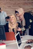 Two woman with hijab working on laptop in office. Royalty Free Stock Photography