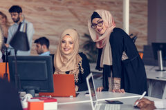 Two woman with hijab working on laptop in office. Stock Photo