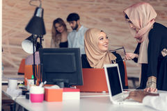 Two woman with hijab working on laptop in office. Stock Image