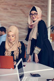 Two woman with hijab working on laptop in office. Stock Photos