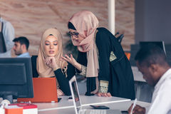 Two woman with hijab working on laptop in office. Royalty Free Stock Images