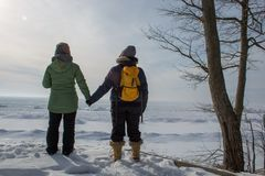 Two woman holding hands with backs turned. Two women holding hands with backs turned on frozen lake shore in the winter Stock Images