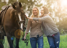 Two woman and horse at a farm. Two women walking with horse at a farm Stock Photo