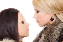 Two woman isolated fur black blond close eye. Makeup royalty free stock image