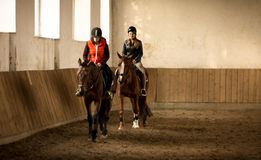 Two woman jockeys doing training in riding hall Royalty Free Stock Image