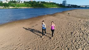 Two woman jogging along the sandy beach of the river at sunset. Beautiful city view. stock video footage