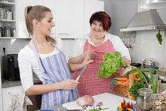 Two woman in the kitchen - one slim, one fat - healthy eating Royalty Free Stock Photo