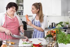 Two woman in the kitchen - one slim, one fat - healthy eating - Royalty Free Stock Photography