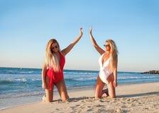 Two Woman Kneeling on White Sand Beach royalty free stock photos