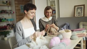 Two woman knitter working together in textile workshop. Woman leisure knitting. Two woman knitter working together in textile workshop. Woman knitter making wool stock footage