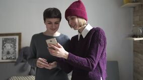 Two woman laughing using mobile phone in room. Woman gossip. Digital lifestyle. Smiling woman looking photo in mobile phone and gossip. Two woman laughing using stock video footage