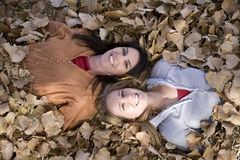 Two woman in leaves eyes open Stock Images