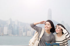 Two woman look somewhere. Two beauty women take map and look somewhere in hongkong Stock Photos