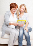 Two woman looking at photo frame Stock Images