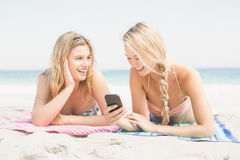 Two woman lying on the beach and looking at mobile phone Stock Photos