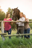 Two woman and man standing with horse at a fence. Two women and men standing on farmland with horse at a fence Stock Photos