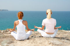 Two woman meditating in mountains stock photography