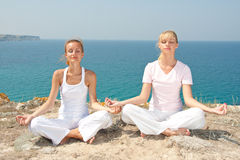 Two woman meditating in mountains Stock Images