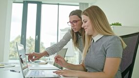 Two Woman Discussing Ideas Using Laptop. Two woman in modern start up office female team leader pointing at screen discussing diverse people group teamwork using stock video footage