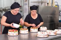 Two woman pastry chefs working together making cakes at the pastry shop. stock photos