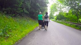 Two woman pushing baby stroller in a rural road stock footage