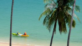 Two woman rowing in canoe on the sea. Thailand stock footage