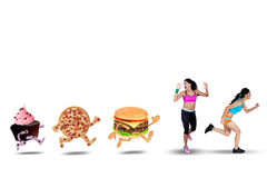Two Woman Running Away from Junk Food Royalty Free Stock Image