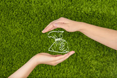 Two Woman's open hands making a protecting money bag. Two Woman's open hands making a protection gesture  on green background holding a money bag symbol.Protect Stock Photography