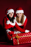 Two woman in Santa costume opening christmas gift. Stock Image