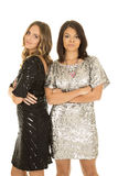 Two woman in shiny dresses stand arms folded Stock Image