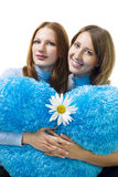 Two woman sit with camomile and teddy heart Stock Photos
