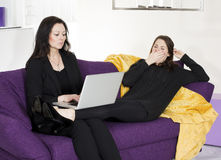 Two woman sitting on couch with a laptop Stock Photo