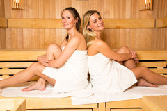 Two woman sitting and posing in a wellness sauna Stock Photography