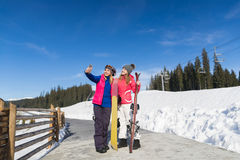Two Woman Ski And Snowboard Resort Winter Snow Mountain Girls Taking Selfie Photo Smart Phone. Holiday Extreme Sport Vacation Royalty Free Stock Image