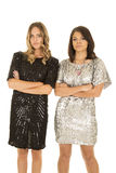 Two woman stand next to each other shiny dresses Stock Image