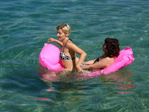Two woman at summer holidays. Two happy woman have a party -  floating on pink mattress at Adriatic sea. Horizontal color photo Stock Photography