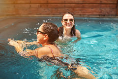 Two woman swimming in pool stock photo