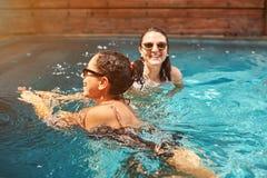 Two woman swimming in pool Stock Photo