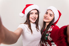 Two woman take selfie from hands in santa hat. royalty free stock image