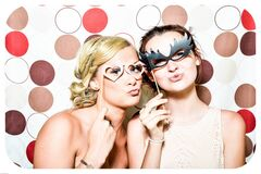 Two Woman Taking Photo in Photobooth Holding Black and Pink Masquerade Mask Stock Images