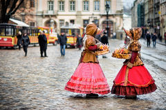 Two woman in traditional clothes standing in the square in old city Stock Photography