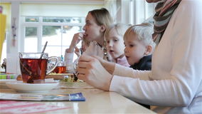 Two woman and two children are eating at the table. stock video