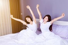 Two woman waking up and hand raised on bed in bedroom Stock Image