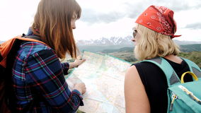 Two woman wanderers exploring map while sitting on a mountain hill in sunny summer day during their weekend,two. Travelers searching road on atlas while taking stock footage