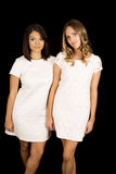 Two woman in white dresses standing black back Stock Photography