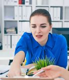 Two woman working at the office while one is pointing at the data at clipboard. Startup concept Stock Photos