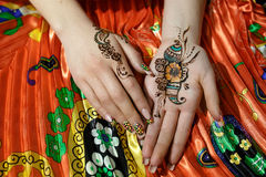 Two womans hands mehendi picture orange bright fabric with pleats. Indian picture on hands palms, mehendi tradition decoration, resistant design by special paint Stock Photos