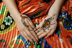 Two womans hands mehendi picture orange bright fabric with pleats Stock Photo