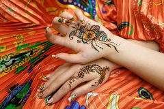 Two womans hands mehendi picture orange bright fabric with pleats. Indian picture on hands palms, mehendi tradition decoration, resistant design by special paint Royalty Free Stock Photography